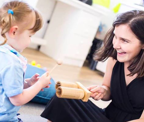 Toddler enjoying playing a musical instrument at Wriggle and Rhyme Meadowridge