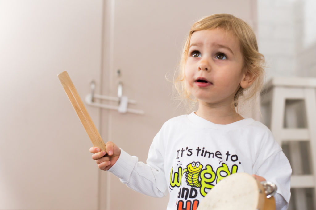 Toddler playing a drum at a music class in Meadowridge