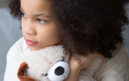 Little girl cuddling her teddy